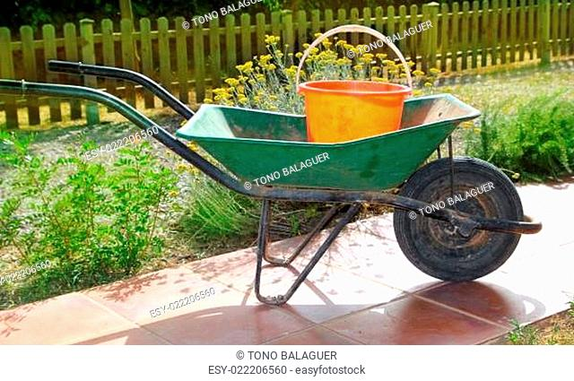 gardener green wheel barrow with orange pail