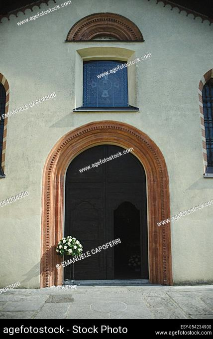 Church door with flowers, Brunello, Varese, Italy