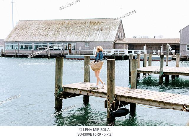 Young woman strolling on wooden pier, Menemsha, Martha's Vineyard, Massachusetts, USA