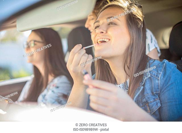 Young woman in car with two friends, looking in rear view mirror, applying lip gloss