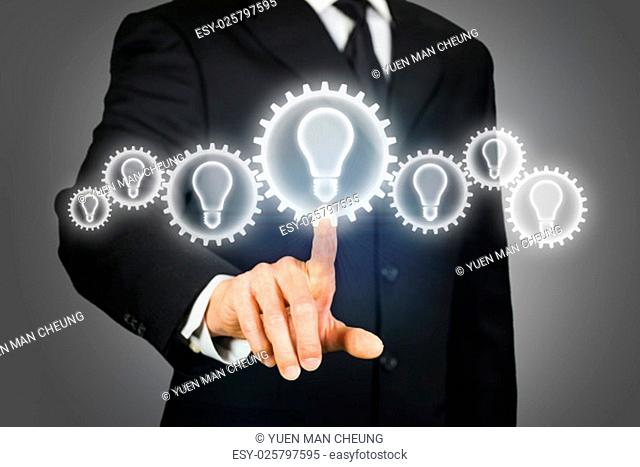 Businessman clicking on a virtual touchscreen with gears with light bulb