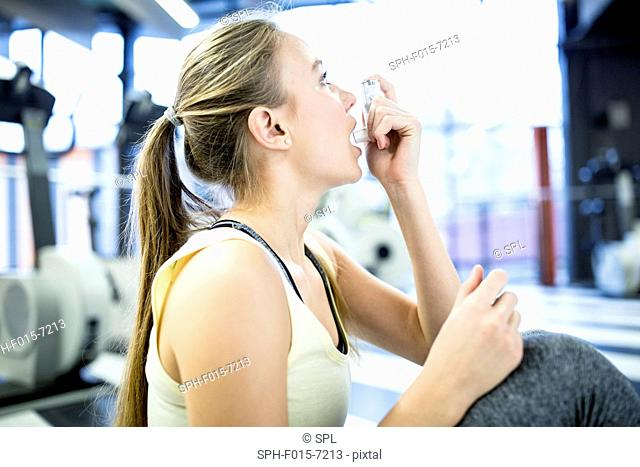 MODEL RELEASED. Young woman using inhaler in gym