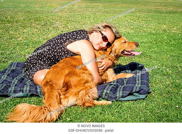 Blonde Woman Hugging Brown Dog on Plaid Blanket on Grass