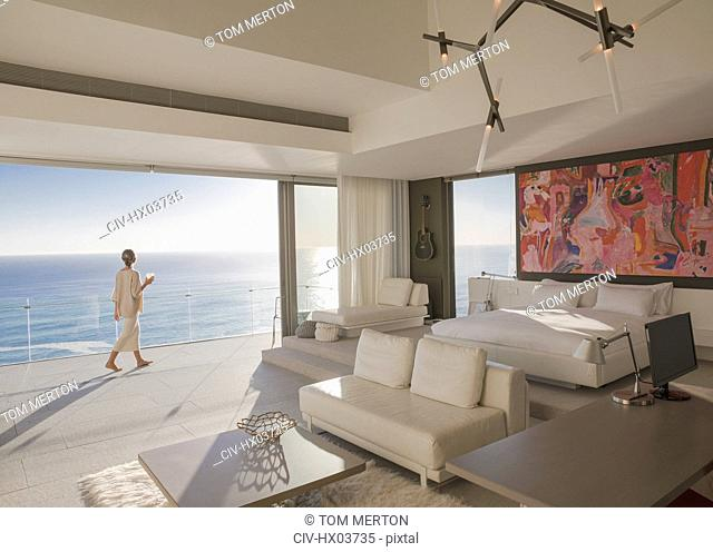 Woman walking on sunny modern, luxury home showcase bedroom balcony with ocean view