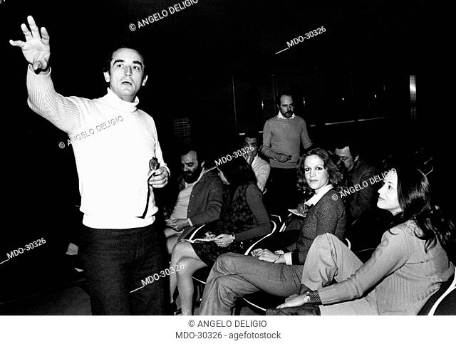 Vittorio Gassman with his daughter Paola. Italian actor Vittorio Gassman talking to his daughter Paola and some other people. Turin, 1970s