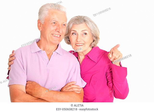 Portrait of a happy senior couple, woman pointing at white background