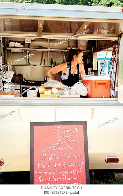 Woman looking out from food stall trailer