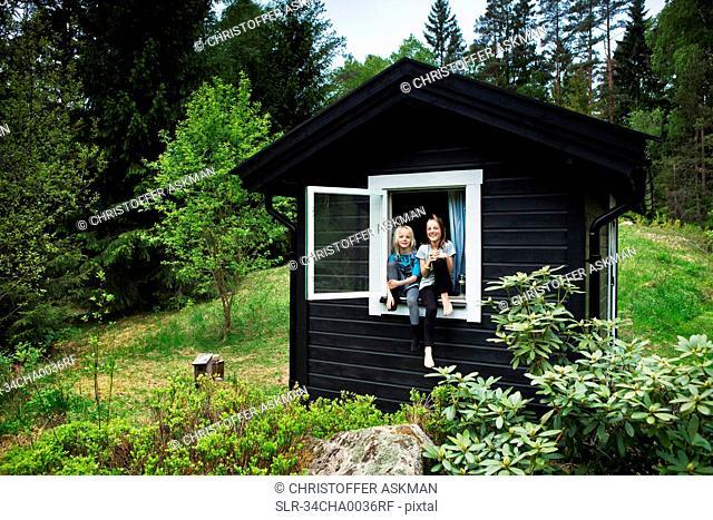 Girls sitting in window of shack