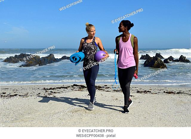 Two women with fitness equipment walking on the beach