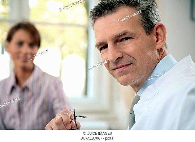 Male doctor with patient in background