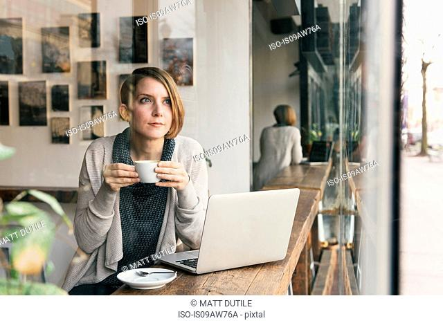 Woman drinking coffee whilst gazing from coffee shop window seat