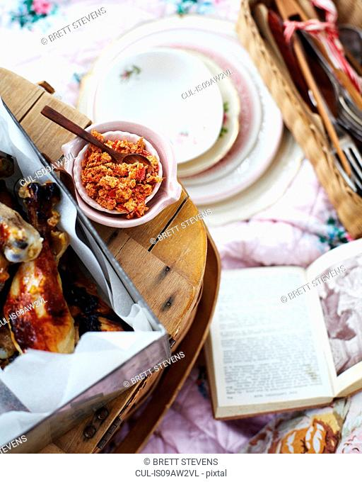 Overhead view of picnic with chicken legs with citrus chilli salt
