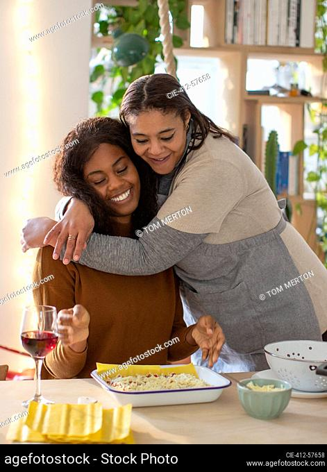 Affectionate mother and daughter hugging and cooking lasagna
