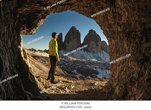 Italy, Tre Cime di Lavaredo, man hiking and standing in front of a cave with the three peaks in background