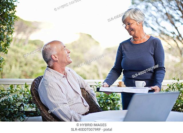 Woman serving husband coffee outdoors