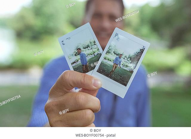 Man's hands holding instant photos