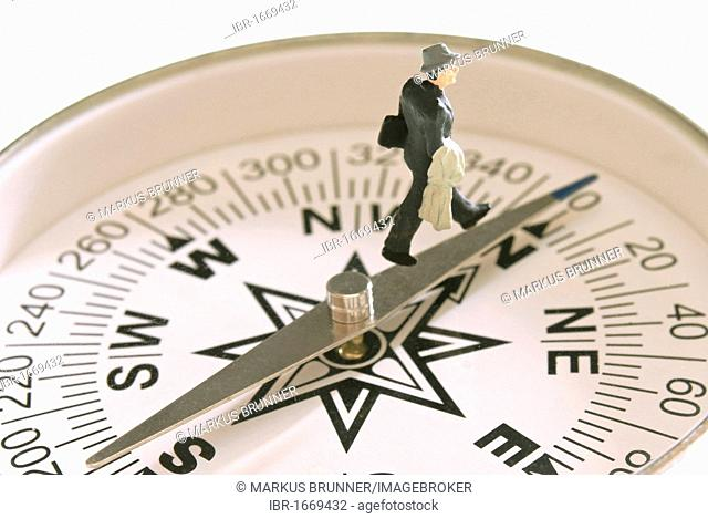 Miniature business man figure walking north on a compass, symbolic image for being on the right course