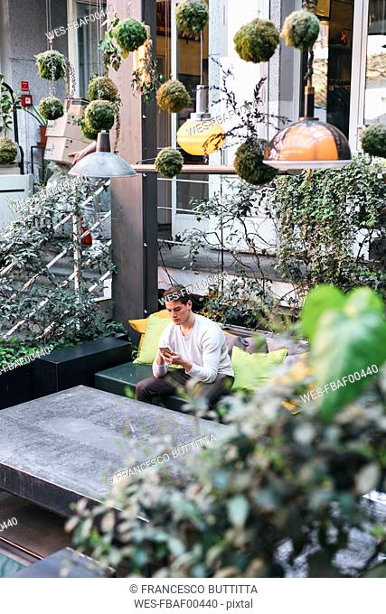 Young man sitting on couch in a stylish cafe using cell phone