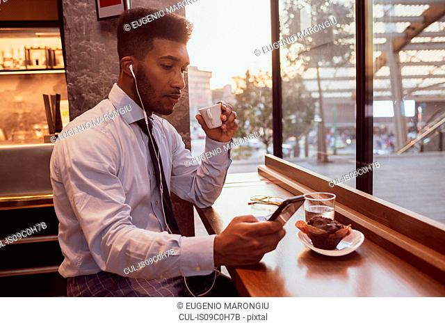 Businessman using smartphone at tea time in cafe
