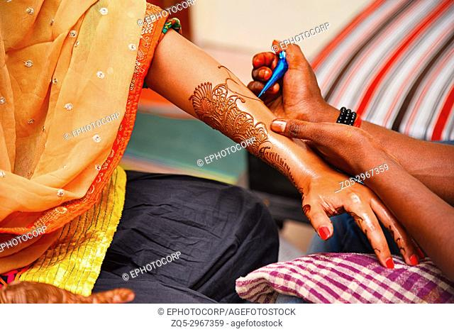 Mehndi (Henna Tattoos) artist drawing mehndi on a lady's left hand at a cultural event, Pune, Maharashtra, India