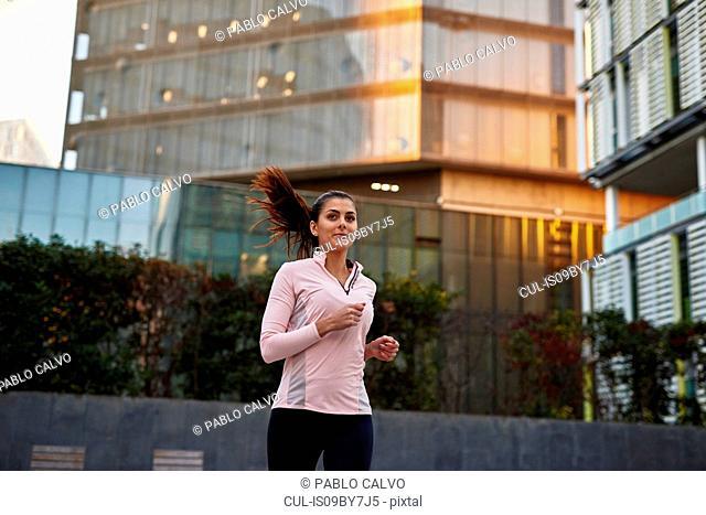 Woman jogging on sidewalk, Barcelona, Catalonia, Spain