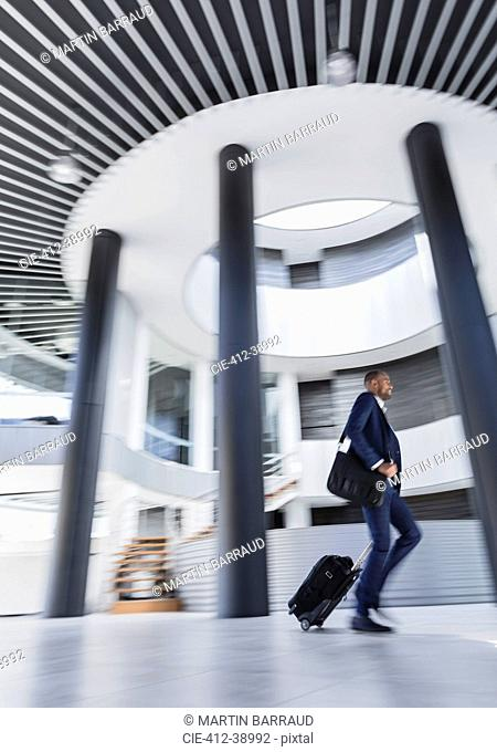 Businessman rushing, pulling suitcase in architectural, modern office lobby