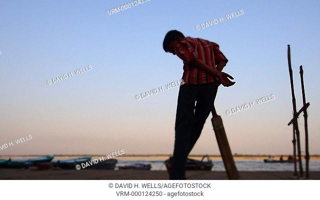 Silhouette of a boy playing cricket in front of a river in Varanasi, Uttar Pradesh, India