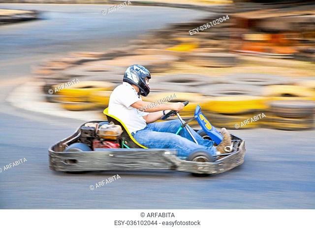 Horizontal take of an Asian driver and go kart as they zoom past on a public race track in Goa India