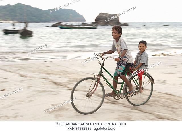 Two boys ride a bicycle at sunset at Ngapali Beach, Myanmar, 10 April 2013. Photo: Sebastian Kahnert | usage worldwide. - Ngapali/Birma