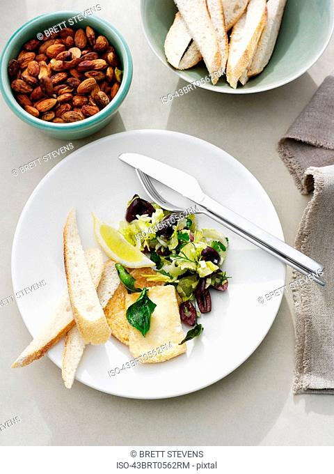 Plates with olives, bread, and nuts