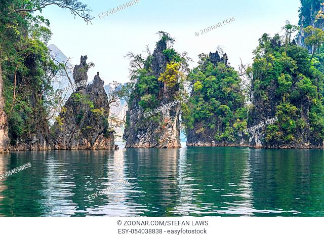 Significant karst formations in the national park Khao Sok rise above the Cheow Lan Lake. Limestone rocks, jungle and karst determine the picture of the nature