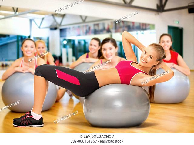 fitness, gym, exercise and health concept - young female instructor doing exercise on fitness ball infront group of people