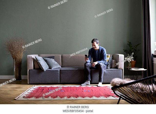 Man sitting on couch in his the living room looking at smartphone