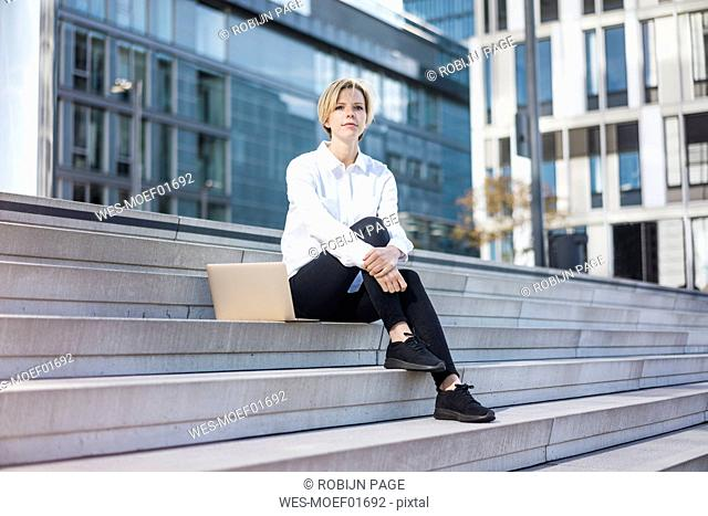 Young businesswman with laptop, sitting on stairs