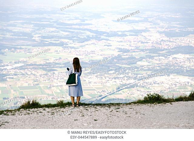 Back view of Young redhead, standing on the path looking towards the valley from the mountain. Untersberg, Salzburgo, Austria