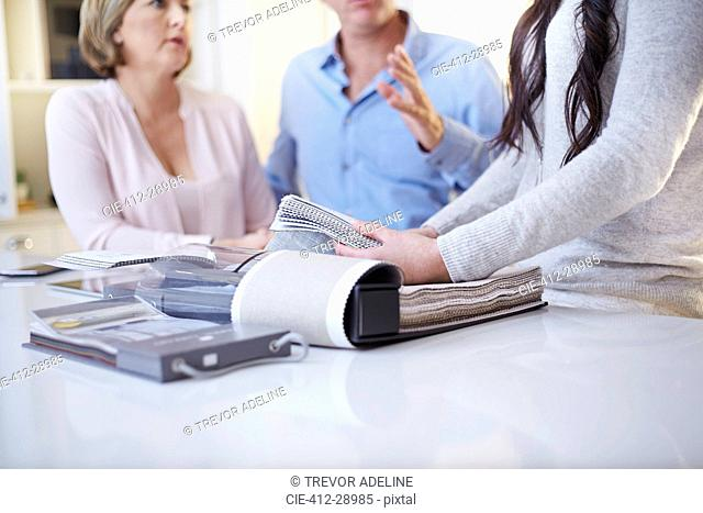 Interior designer discussing swatches with couple in consultation