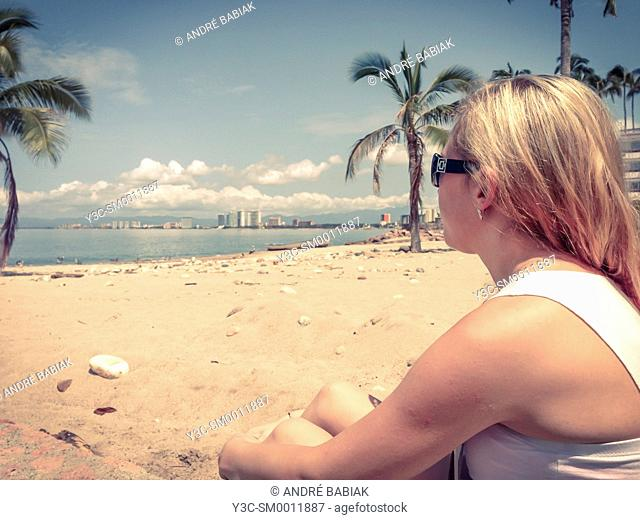 Young woman sitting at a beach in Puerto Vallarta, Mexico