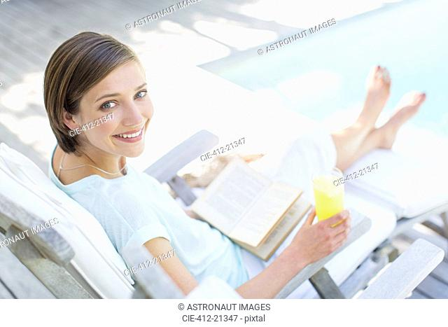 High angle view of woman reading and drinking juice by swimming pool