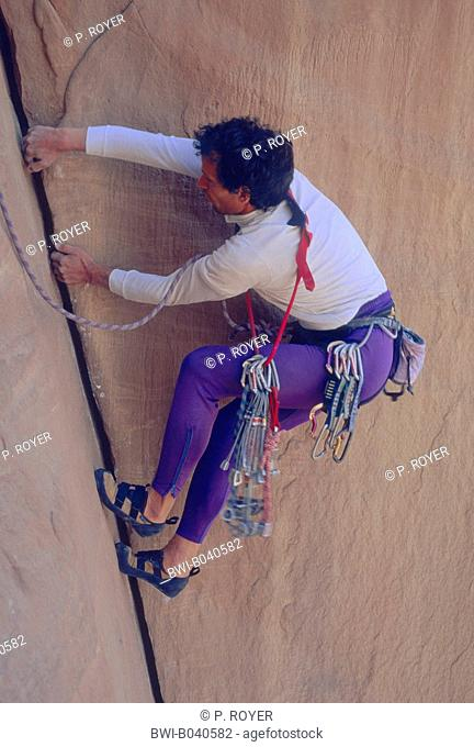 rock climber in a steep face, piazzing along a vertical ledge, Jordan, Wadi Rum
