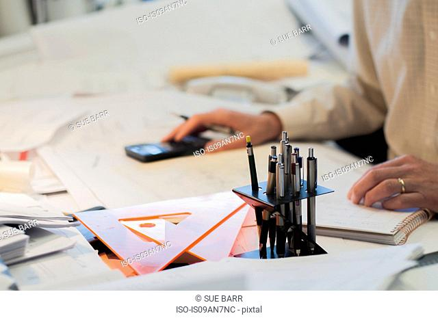 Architect sitting at desk, using calculator, mid section