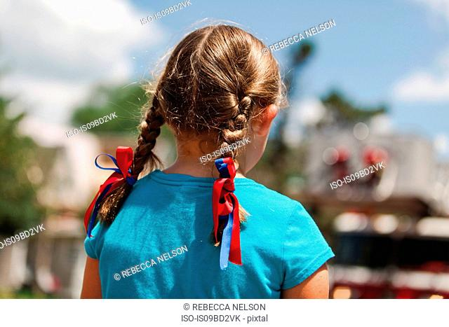 Girl with plaited hair, red and blue ribbons in hair, rear view