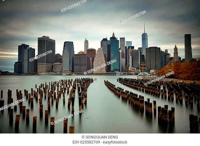 Manhattan financial district with skyscrapers and abandoned pier over East River