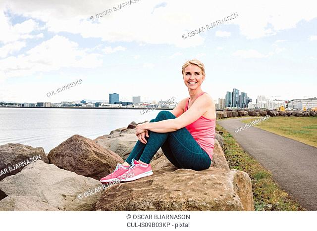 Portrait of female runner sitting on waterfront boulders, Reykjavik, Iceland