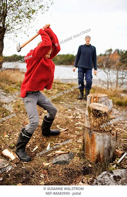 Teenager chopping wood, father watching