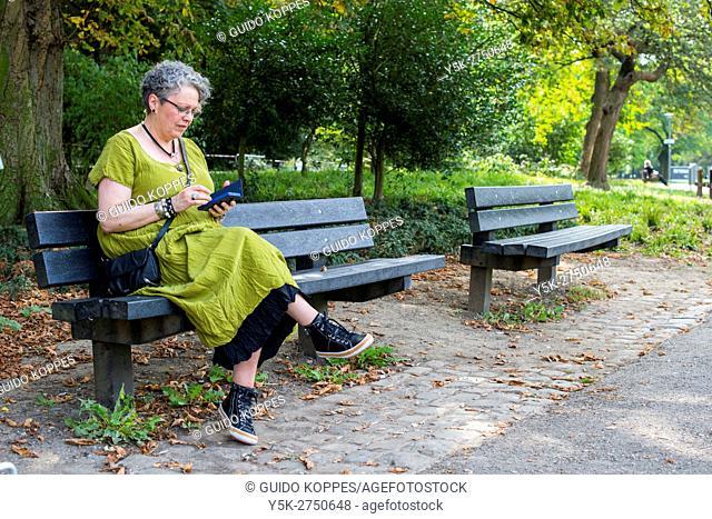 Maastricht, Netherlands. Senior adult woman reading her smartphone e-mails while sitting on a park bench