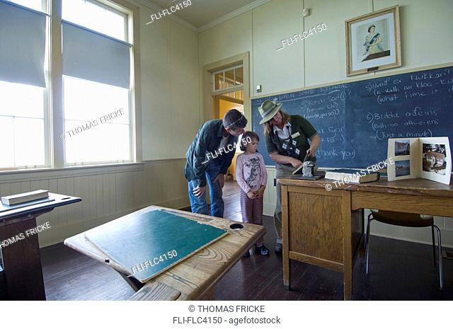 Father with his young daughter and a tour guide in the Hecla School Museum in Hecla Island, Manitoba, Canada