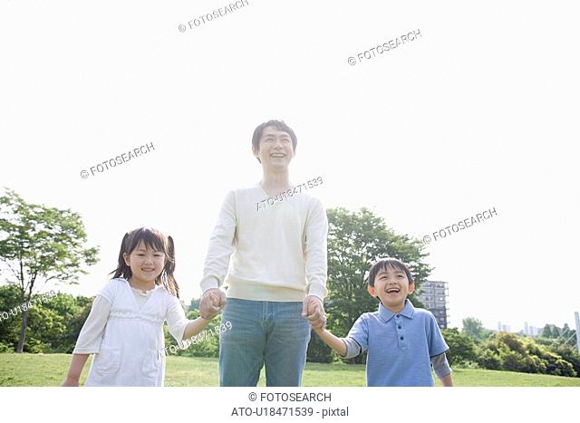 Father with Two Children Holding Hands