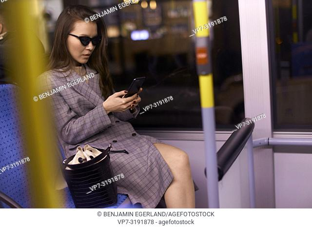 Woman in tram by night. Munich, Germany