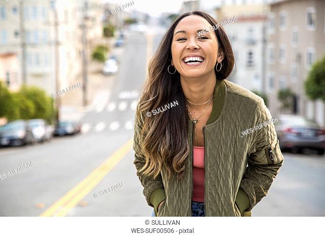 Portrait of laughing young woman on the street