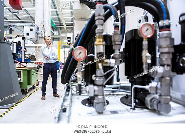 Man in factory shop floor looking at machine